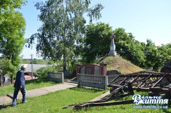 Біля пам'ятного хреста в Кліводині замість квітів і свічок — борона і сівалка